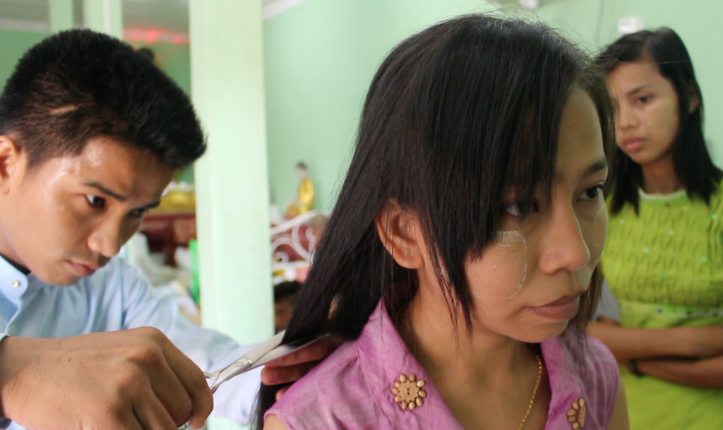 A lady cuts her hair to donate to the 'Gold Hair bridge' project. (Photo: Libby Hogan / DVB)